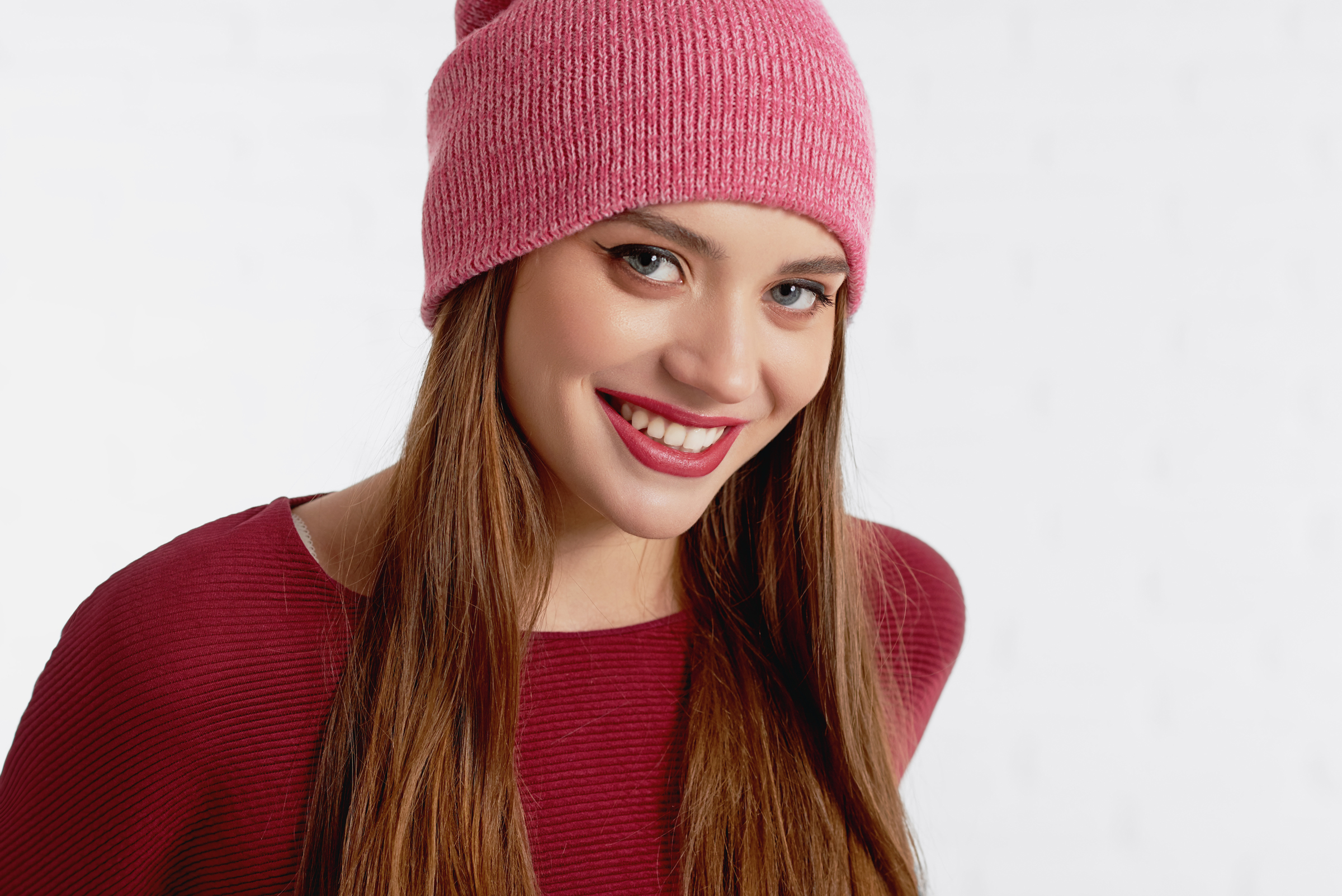 Smiling attractive female model in red hat and with make up